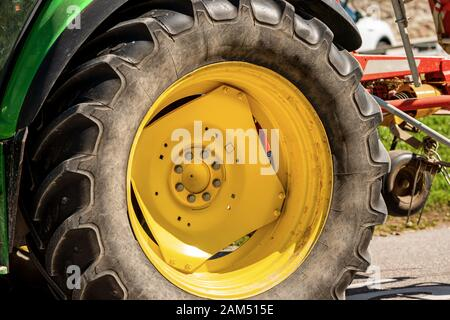 Close-up of a large yellow wheel of a tractor with black tire, agricultural machinery - Stock Photo