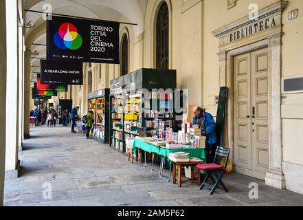 Glimpse of the second-hand book market under the arcades of Via Po street in the historic centre of Turin with people in a winter day, Piedmont, Italy - Stock Photo