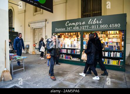 Glimpse of the second-hand book market in front of Rectorate Palace under the arcades of Via Po street with people in a winter day, Piedmont, Italy - Stock Photo
