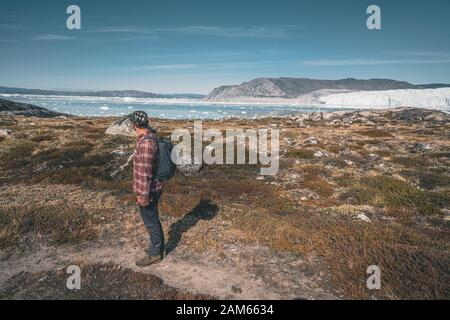 A young man traveler tourist standing in front of Eqip Sermia glacier called Eqi Glacier. Wall of ice in background. The concept of global warming and - Stock Photo
