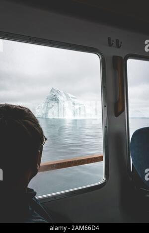 Tourist Looking at Glaciers and icebergs Mountains on a boat in west greenland. Iceberg in sea and ocean. Overcast day. Male traveler. - Stock Photo