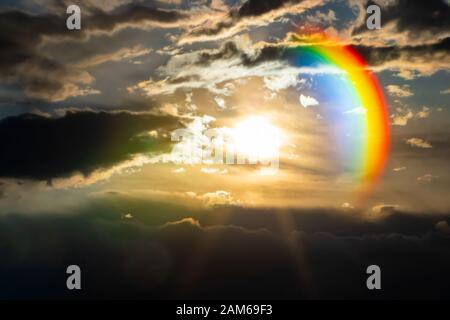 Wide shot of cloudy sky with lens flares. Sun shining through dark clouds. View from above. Start of new day, new life concepts