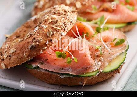 Two bagel sandwiches with sliced salt salmon, cream cheese, cucumber, and micro greens closeup - Stock Photo