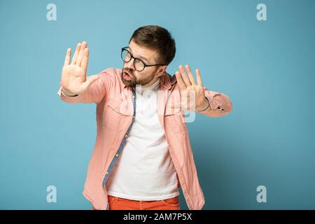 Man reassures someone by making a stop gesture with hand, holding palms forward and looking seriously at the camera. - Stock Photo