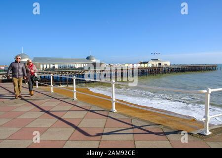 Couple strolling along Hastings seafront promenade in front of the pier; under cloudless skies, on a sunny winter day, East Sussex, UK - Stock Photo