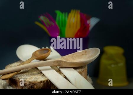 Rustic wooden utensils in a kitchen still life with two spoons and colorful plastic forks over a weathered log of wood on hessian - Stock Photo