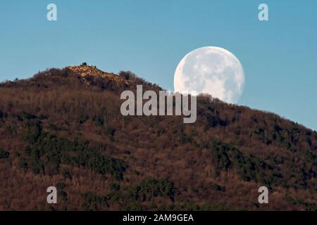 The full moon sets early in the morning behind a mountain against the blue sky - Stock Photo