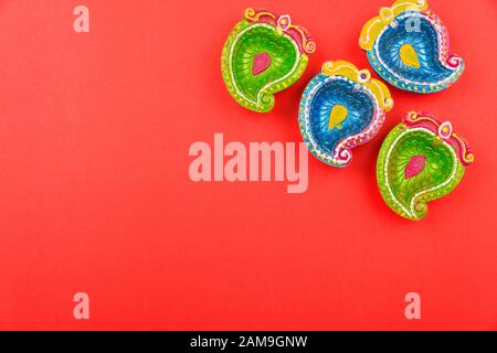 Happy Diwali Day, Flat lay top view Colorful Clay Diya lamps on red background and copy space for your text - Stock Photo