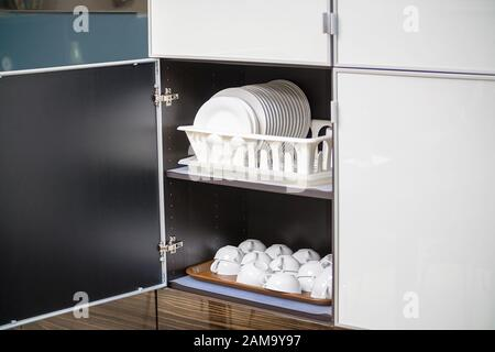 White clean plates and coffee cups in the cupboard on the shelf - Stock Photo