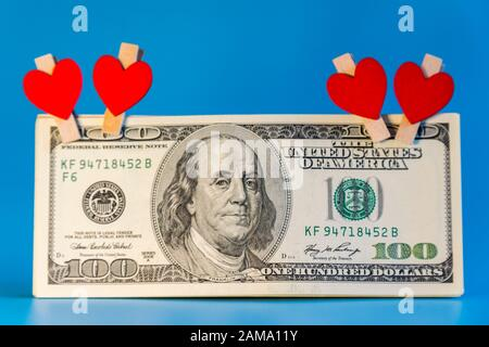 One hundred dollar bill in hearts on a blue background. - Stock Photo