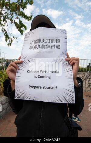 January 12 2020 Central Hong Kong. Karma_to_Commies_Rally. A man_holds a_poster warning_of the virus from China - Stock Photo