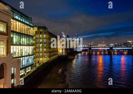 Looking west from London Bridge along the River Thames towards Cannon Street Railway Bridge at night with illuminated offices on the South Bank, UK - Stock Photo
