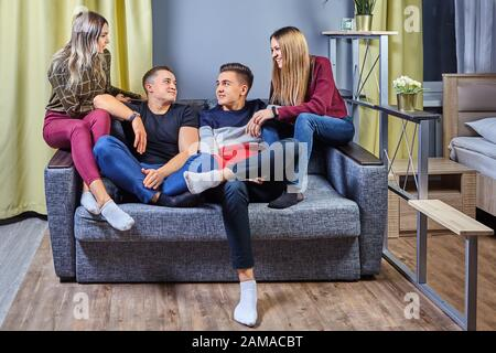 Two young men are sitting on the couch in front of the TV, the girls distract their boyfriends from watching the movie, they want to communicate, and - Stock Photo