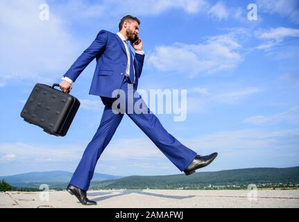 Businessman formal suit carries briefcase sky background. Businessman solving business problems on phone. Never stop. Keep going towards your goal. Entrepreneur in motion purposeful expression.
