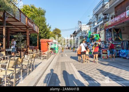STAVROS, GREECE - AUGUST 19, 2019: Main pedestrian street of town of Stavros, Chalkidiki, Central Macedonia, Greece - Stock Photo