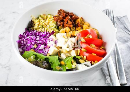 Vegetarian buddha bowl. Raw vegetables, tofu and bulgur in white bowl. Vegetarian, healthy, detox food concept, close-up - Stock Photo