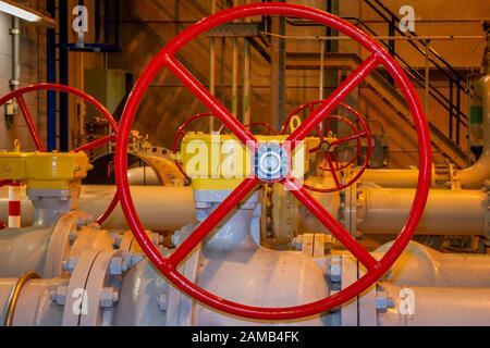 Red painted hand wheels for opening or close the hand valves in the industrial pipes - Stock Photo