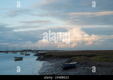 Early evening at Brancaster Staithes in North Norfolk looking out towards the sea with yachts and a background of sunlit clouds and pale blue sky - Stock Photo