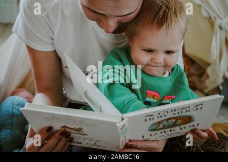 Young child reading with their mum - Stock Photo