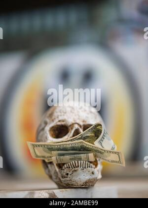 Human skull holding money peace sign spray painted on background graffiti on wall greed for wealth - Stock Photo