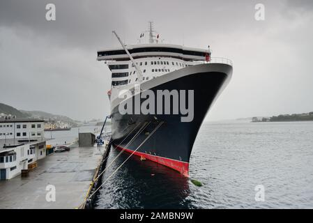 Cunard liner Queen Mary II berthed at Alesund on a wet and overcast day. - Stock Photo