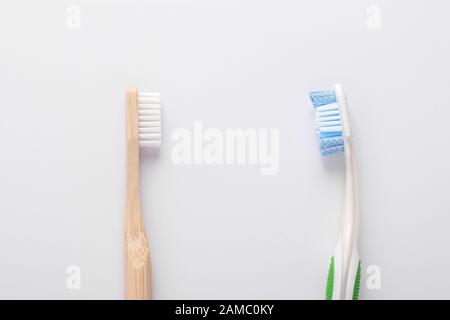Zero waste concept, Eco wooden toothbrush vs plastic toothbrush on white background: Reduce, Reuse and Recycle concept. Flat lay, Closeup, Horizontal - Stock Photo