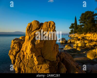 Sunset lighted light on boulder rock on beach seaside Malinska on island Krk in Croatia Europe - Stock Photo