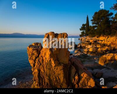 Sunset lighted light on boulder rock on beach seaside before coastline promenade Malinska on island Krk in Croatia Europe - Stock Photo
