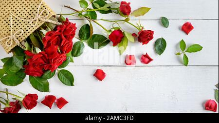 Flowers composition. Red roses on a white wooden background. Flat lay, top view. Free space for text. - Stock Photo