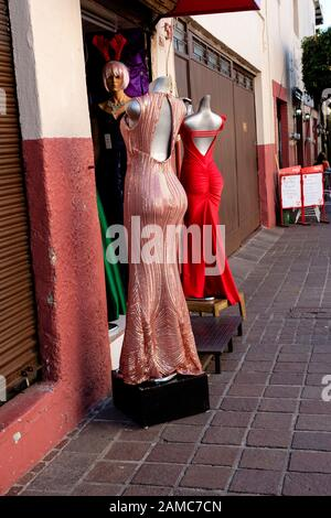mannequins on display on a Mexican sidewalk with elegant evening gowns - Stock Photo