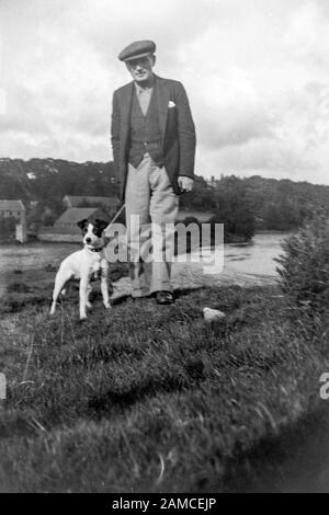 Archive image of a man and his dog, circa 1920s scanned directly from the negative - Stock Photo
