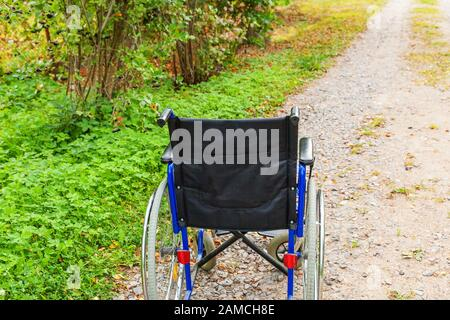 Empty wheelchair standing on road in hospital park waiting for patient services. Invalid chair for disabled people parked outdoor in nature. Handicap accessible symbol. Health care medical concept - Stock Photo