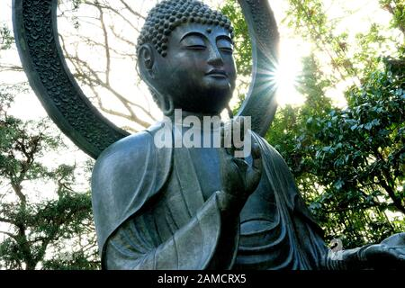Detail of the Buddha statue in the Japanese Garden, Golden Gate Park, San Francisco, California, USA with the sun breaking through trees background. - Stock Photo