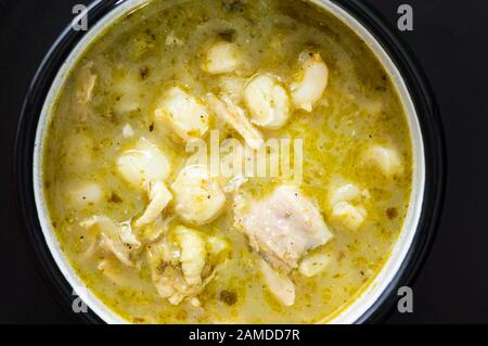 Pozole verde, or green posole is traditionally made with hominy and meat and topped with condiments. Mexican cuisine. - Stock Photo