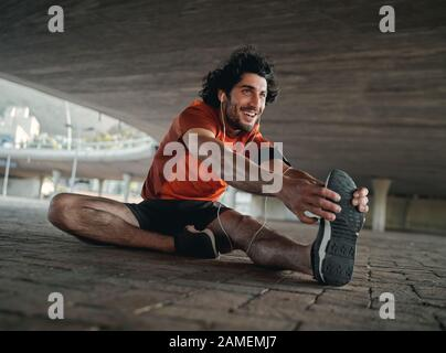 Portrait of a smiling young man athlete in earphone sitting under the city bridge stretching his legs before jogging
