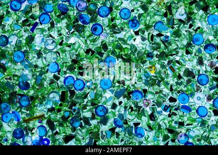 Abstract background of close up detail of fragments of green and blue crushed glass and beads backlit - Stock Photo