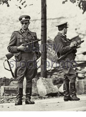 East German border guards on patrol near the Berlin wall. GDR, East Germany, 1960-e The Berlin Wall (Berliner Mauer) was a guarded concrete barrier th Stock Photo