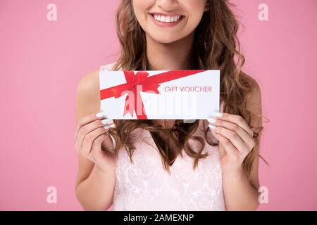 Close up of beautiful woman giving a gift voucher - Stock Photo
