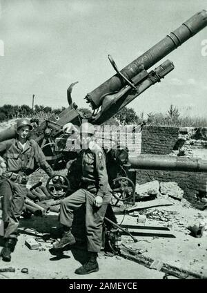 Robert Myers (left) and Sergeant Spradling of the 275th Infantry Regiment of the US Army are posing next to the destroyed German 88-mm anti-aircraft g - Stock Photo