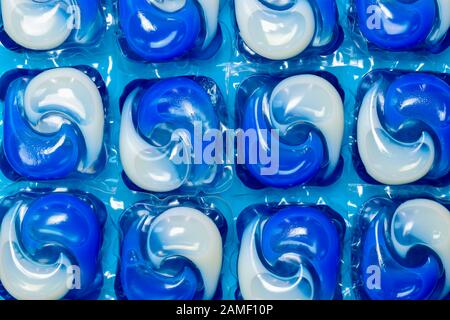 Close up detail of blue and white washing machine liquid detergent laundry capsules/pods isolated against a blue background - Stock Photo