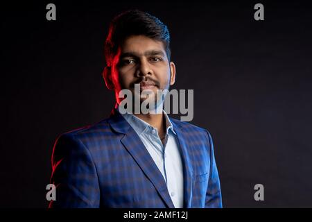 Closeup portrait of young handsome confident serious bearded Indian businessman with stylish haircut, wearing shirt, checked suit, looking at camera, - Stock Photo