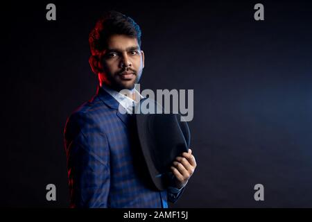 Closeup portrait of young handsome confident serious bearded Indian man, businessman with stylish hairstyle, wearing shirt, checkered suit standing ag - Stock Photo