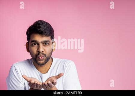 Handsome indian male blowing air kiss, expressing his love, sympathy to girlfriend, wearing casual white t shirt, isolated over pink background with c - Stock Photo