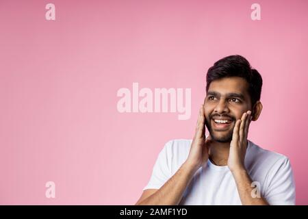 Portrait of pleasantly surprised happy man in white t shirt, touching cheeks with palms, looking aside with amazed expression, isolated on pink backgr