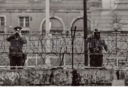 East German border guards on the Berlin wall. The Berlin Wall (Berliner Mauer) was a guarded concrete barrier that physically and ideologically divide Stock Photo