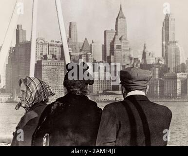 An immigrant family looks out over the New York skyline as they arrive in the USA from Germany aboard the S. S. Nieuw Amsterdam. Lower Manhattan, New - Stock Photo