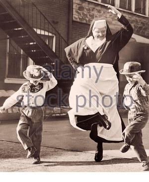 Nun Dancing with Children in jig time for St. Patrick's day. March 14, 1964 St. Louis, Missouri, USA - Stock Photo