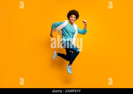 Full size photo of crazy funny funky afro american girl jump run hurry wear white turquoise sweater autumn blue stylish trendy outfit isolated over - Stock Photo