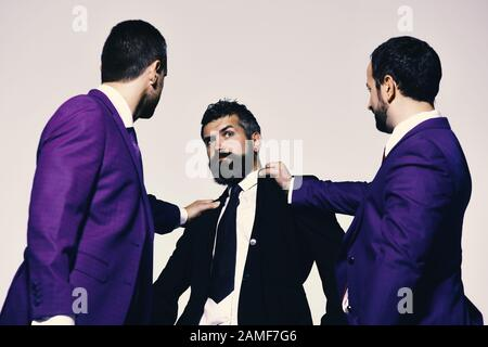 Coworkers push weaker colleague down. Company leaders fight for business leadership. Business conflict and argument concept. Businessmen with confident faces in formal suits on grey background. - Stock Photo