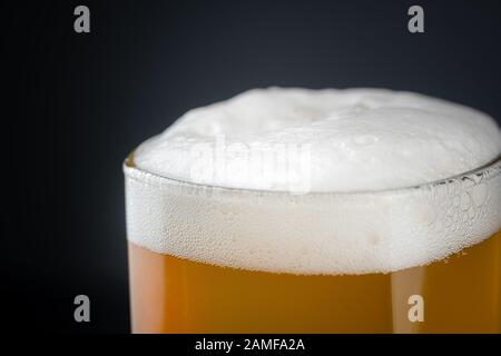 Fresh and cold glass craft beer with white foam on top on black background with space for text. Foamy wheat or lager beer on dark background - Stock Photo